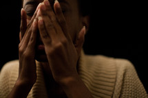 African-American woman covering her face with her hands