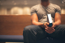 man holding a Bible sitting in a church pew in prayer