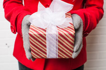 hands in gloves holding a wrapped Christmas gift