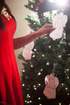 an African-American woman touching an angel ornament on a Christmas tree