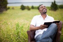man sitting in a chair outdoors in a field reading a Bible smiling