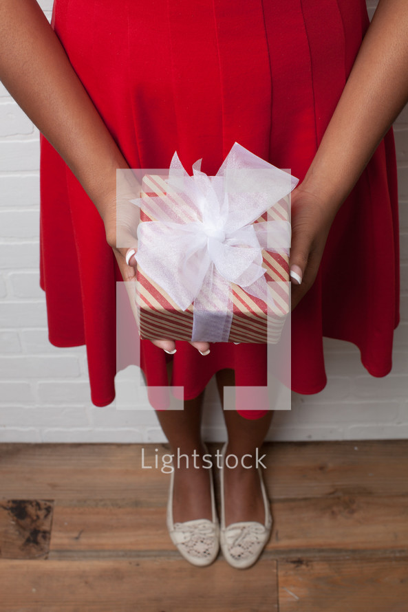 An African-American woman holding a wrapped Christmas gift