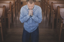 man kneeling in prayer in the aisle of a church
