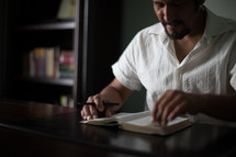 Man with a pen turning the pages of a Bible on a wooden table.