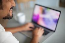 Smiling man typing on a laptop computer.