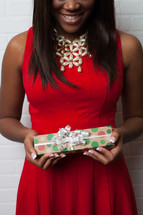 An African-American woman in a red dress holding a Christmas gift