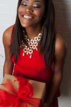 An african-american woman holding a wrapped gift