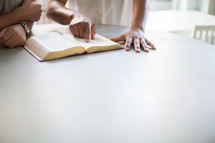 Two people studying a Bible at a table.