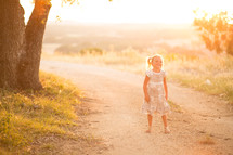 A young girl standing on a dirt road on a sunny day