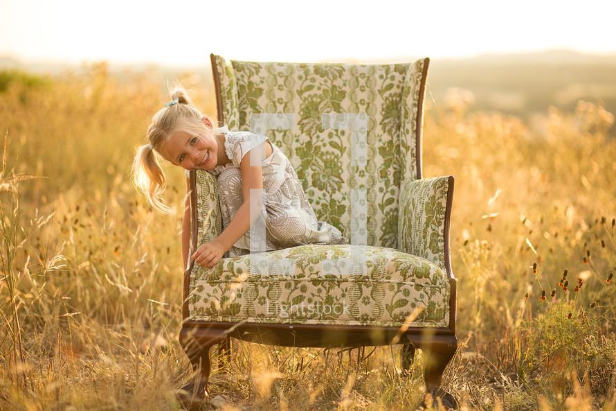 Happy girl sitting on big chair in open field
