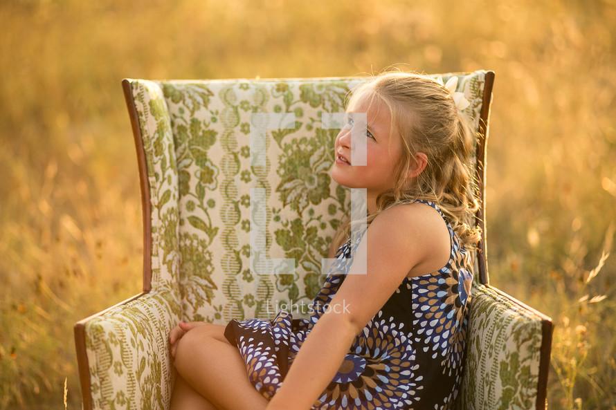 girl sitting in a armchair in a field