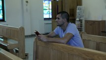 a man kneeling reading a Bible in a church