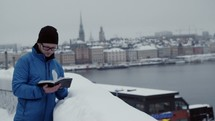 a man reading a Bible standing outdoors near a harbor in the snow