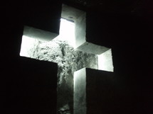 A brightly lit cross on a black background.
