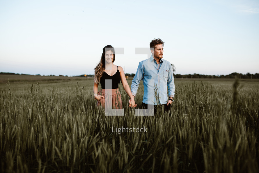 a couple holding hands in a field of wheat
