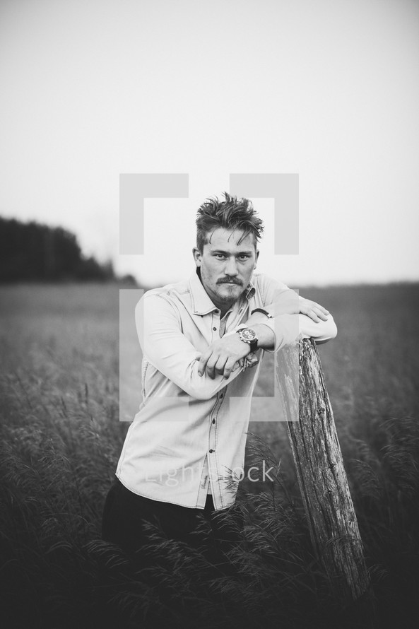a man posing in a field