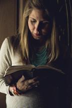 a pregnant woman reading a Bible