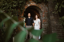 a couple standing under a brick arch