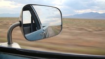 rearview mirror view as a car drives on a desert road