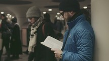 A man reading a Bible in a crowded subway station