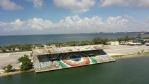 Cinematic Aerial Orbiting Pan around an abandon boating stadium with water and city skyline in Miami 4k