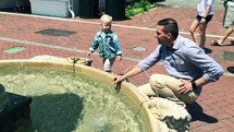 a father and son playing in a fountain