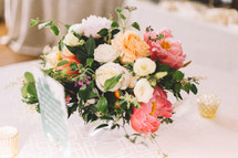 flower arrangement at the center of a table at a wedding reception