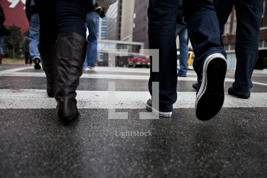feet walking on a city crosswalk