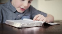 Child reading a Bible out loud to himself.