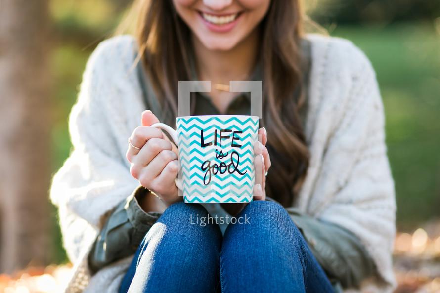 a woman holding a life is good mug