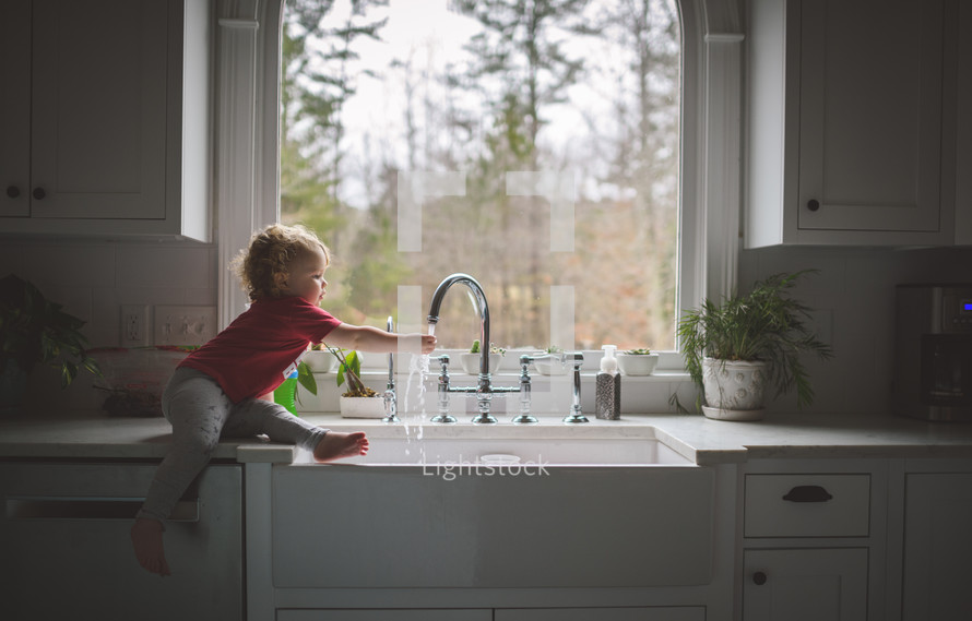 toddler playing in water at the kitchen sink