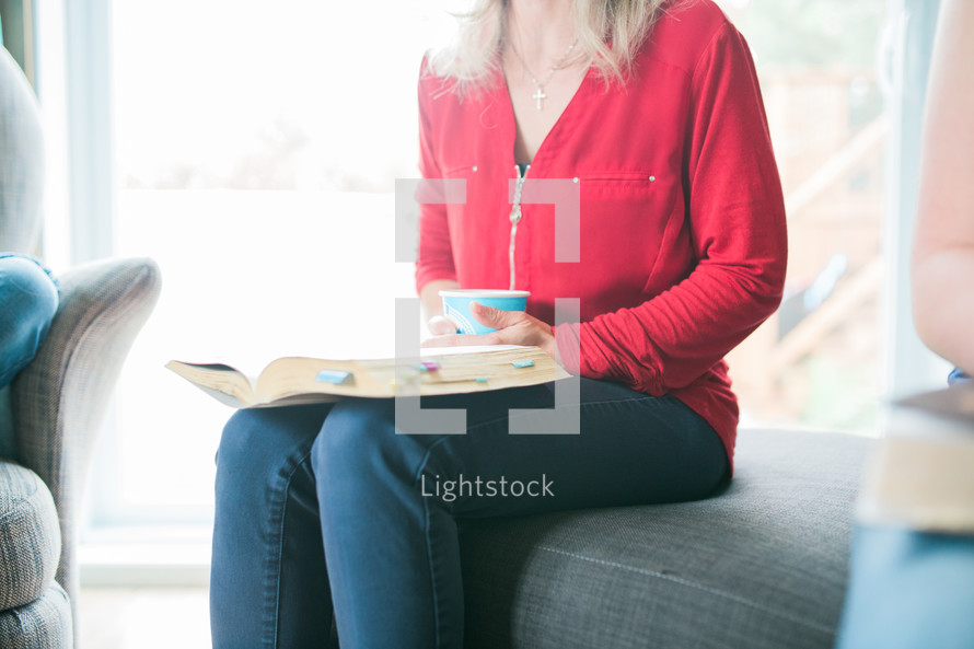 a woman sitting on a couch drinking coffee and reading a Bible