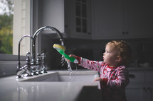 a toddler girl wetting a sponge in a kitchen sink