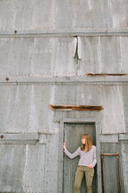 a woman standing in front of a building made of sheet metal