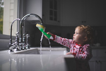 toddler girl playing with a sponge in a kitchen sink