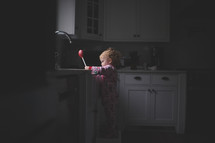 toddler girl playing in a kitchen sink