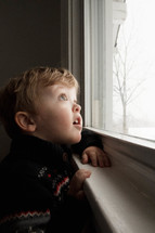 toddler boy looking out a window