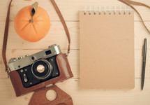 orange, camera, notepad, and pen