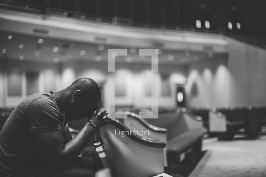 man with his head bowed in prayer in an empty church