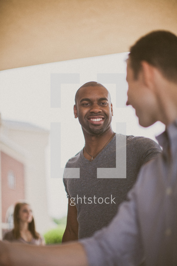 Smiling men talking.