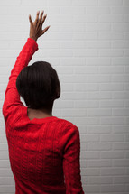 African-American woman with hand raised praising God