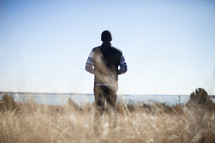 man standing in a field by a lake