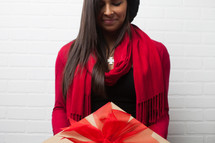 an African American woman with head bowed holding a wrapped Christmas gift
