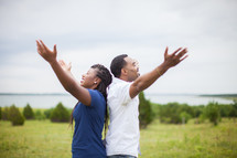 couple with raised hands praising God