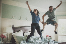 couple jumping on a bed
