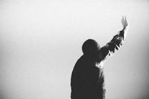 A man raises his hand above his head under a gray sky.