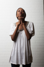African-American woman with praying hands looking to God