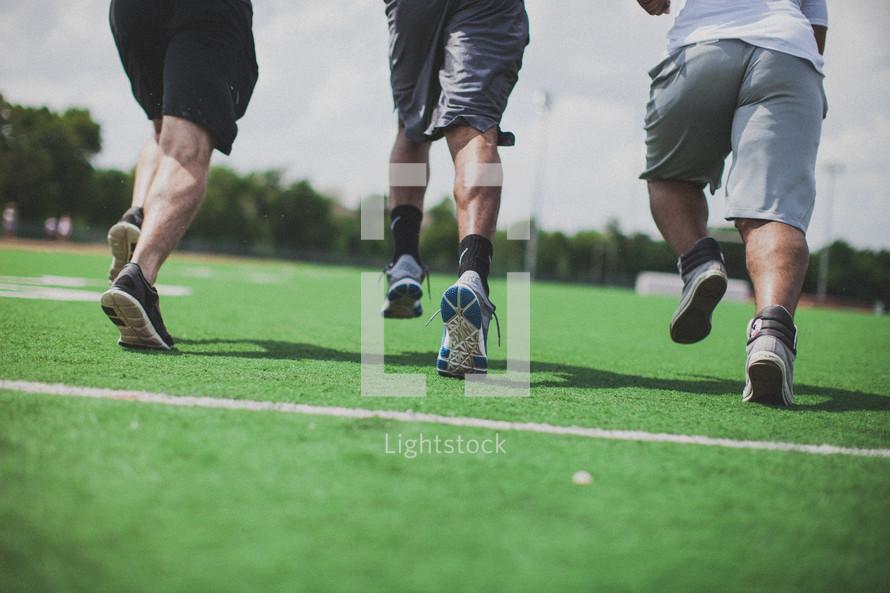 men running on a football field