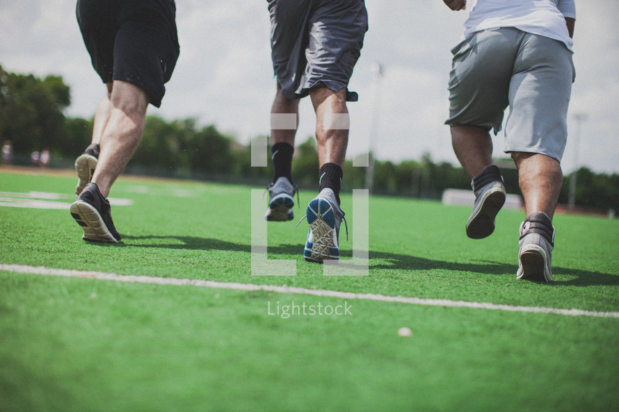 men running on a football field