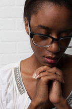 face of an African-American woman with reading glasses and praying hands